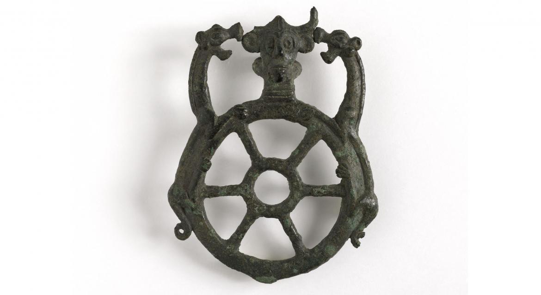Ornement d'harnachement en forme de roue à six bras. Surmonté d'une tête humaine cornue entre deux têtes d'animaux. Bronze. Luristan. IIème-Ier millénaires av. J.-C. Paris, musée Cernuschi.